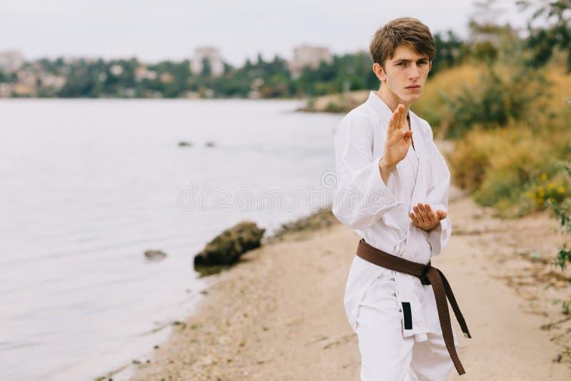 Sportlicher junger Mann auf dem Freienkaratetraining Junge im Kimono auf einem natürlichen Hintergrund Ausübung des Konzeptes stockfotos