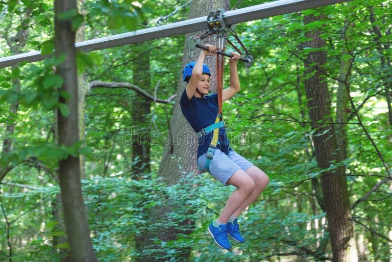 Sportlicher, junger, netter Junge im weißen T-Shirt verbringt seine Zeit im Abenteuerseilpark im Sturzhelm und in der sicheren Au lizenzfreie stockfotos