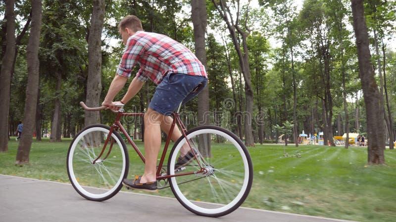 Sportlicher Kerl, der an der Parkstraße radfährt Junger gutaussehender Mann, der Weinlesefahrrad im Freien fährt Gesunder aktiver stockfotos