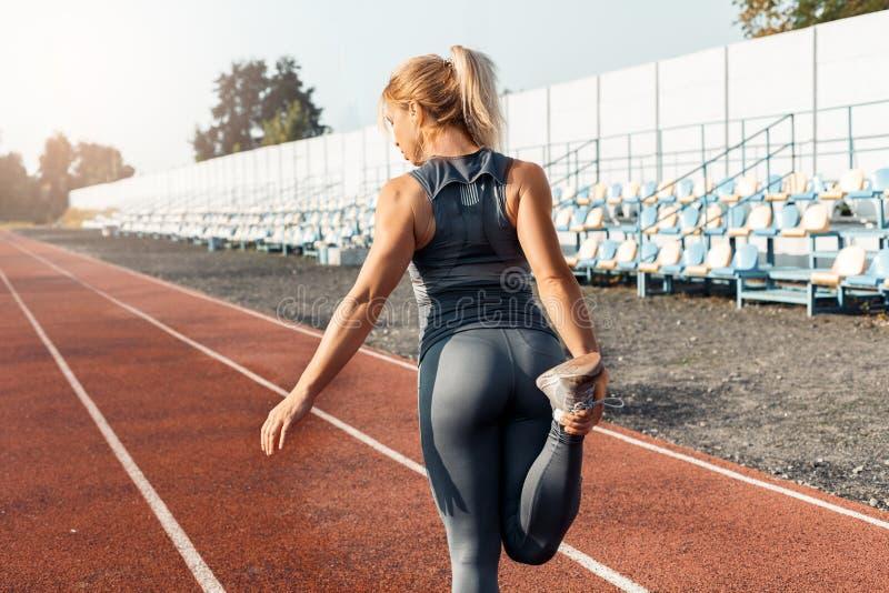 Sportlicher Lebensstil Junge Frau auf der Stadionsstellung, die Bein starke hintere Ansicht ausdehnt stockfoto