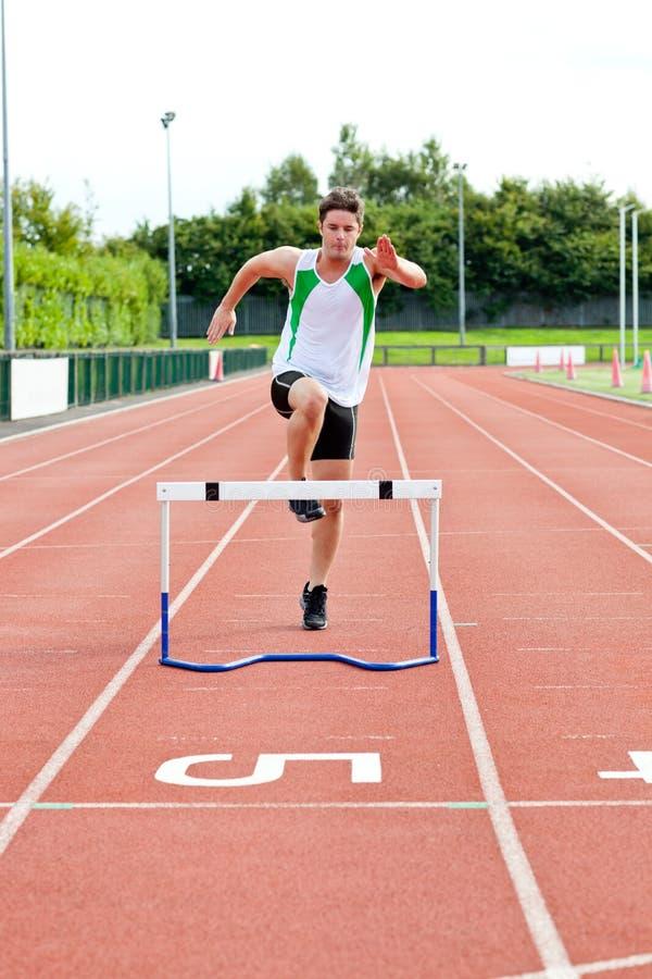 Sportlicher Mann, der über Hecke während eines Rennens springt stockfotos