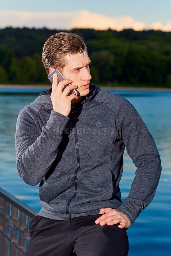Sportlicher Mann, der am Telefon im Park nach der Ausbildung spricht stockfotografie