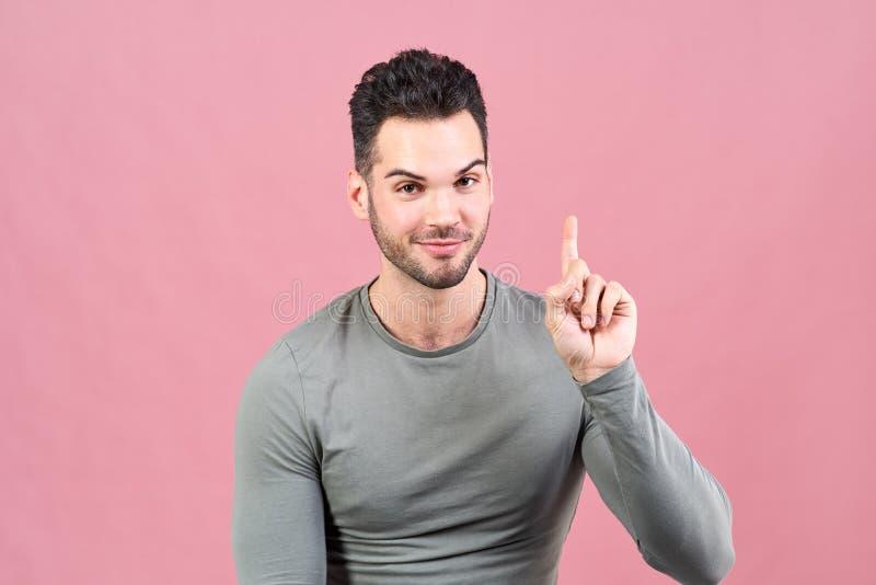 Sportlicher weiß-enthäuteter Mann in einem grauen T-Shirt hebt seinen Finger oben an und informiert Sie enthusiastisch, dass er e lizenzfreie stockfotografie