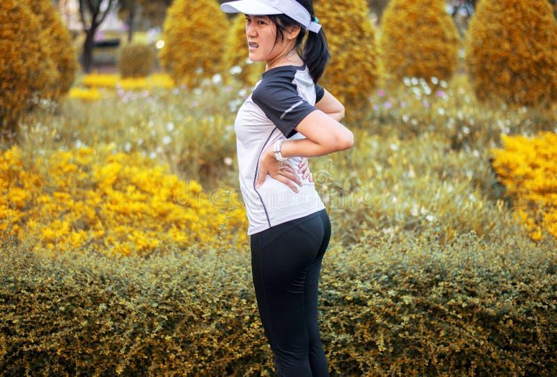 Sportliches asiatisches weibliches Leiden von den Schmerz in der Taillenverletzung nach dem laufenden Rütteln der Sportübung und  stockfotos