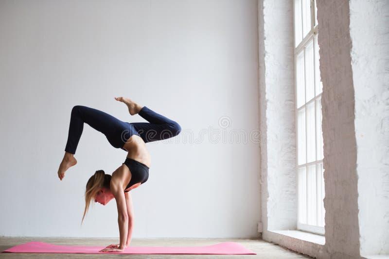 Sportliches Jogimädchen übt Yoga asana, Skorpions-Haltung Vrischikasana lizenzfreie stockfotos