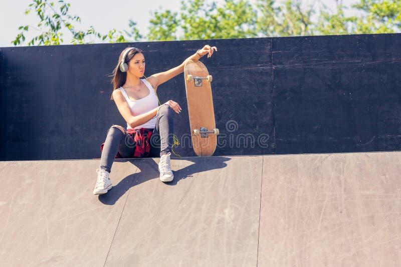 Sportliches jugendlich M?dchen mit h?render Musik des Skateboards Drau?en st?dtischer Lebensstil stockfotografie