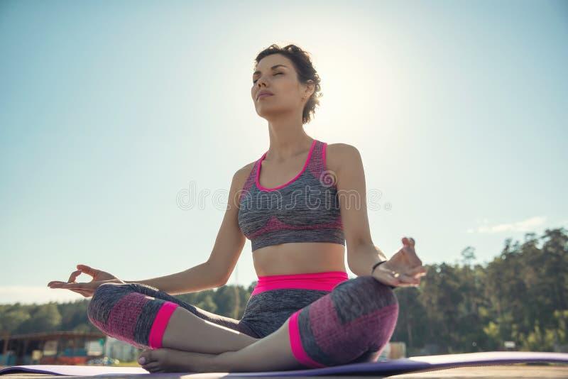 Sportliches junges Mädchen morgens auf dem Pier auf Küste, übendes Yoga Frau tun Gymnastik draußen Gesundheit und Yoga lizenzfreie stockfotografie