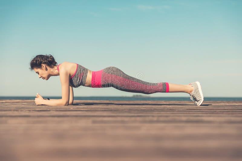 Sportliches junges Mädchen morgens auf dem Pier auf Küste, übendes Yoga Frau tun Gymnastik draußen Gesundheit und Yoga stockbilder