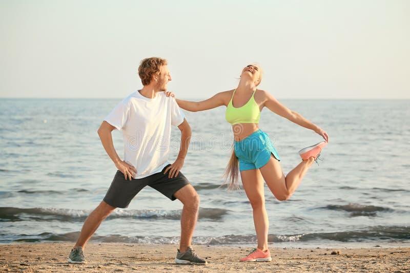 Sportliches junges Paartraining auf Seestrand stockfotos