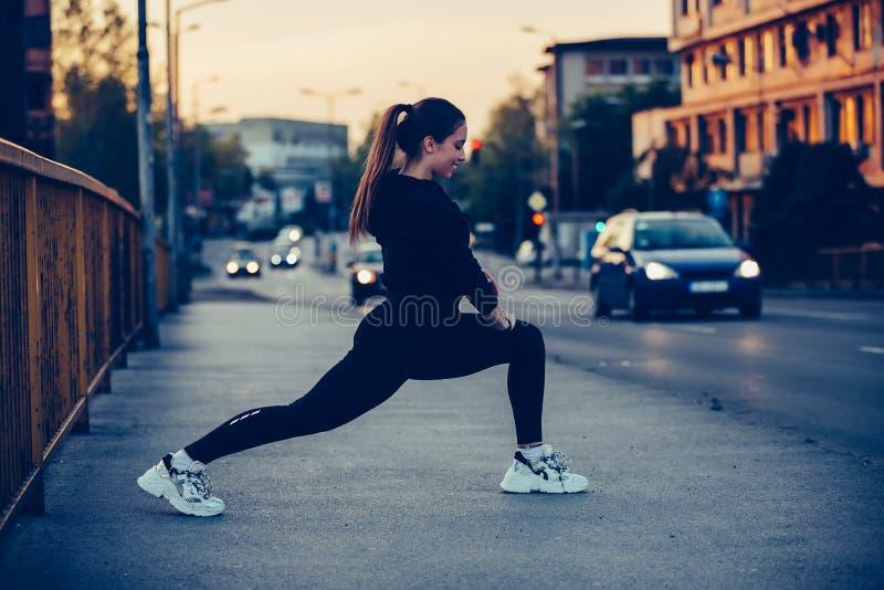 Sportliches Mädchen, das Übung auf der Brücke, nachts ausdehnend tut lizenzfreie stockbilder