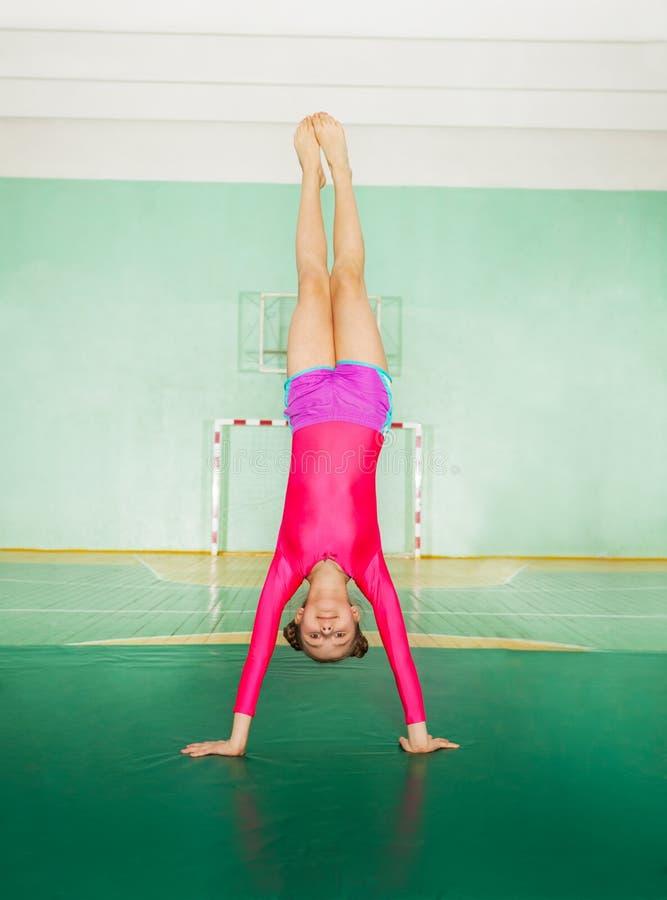 Sportliches Mädchen, das Handstand in der Schulturnhalle tut stockbild