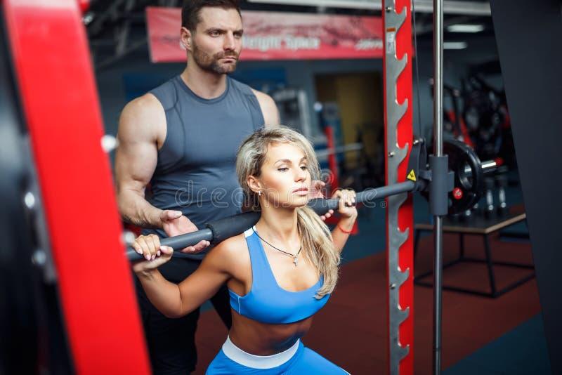 Sportliches Mädchen, das untersetzte Übungen mit Unterstützung ihres persönlichen Trainers an der Turnhalle tut lizenzfreies stockbild