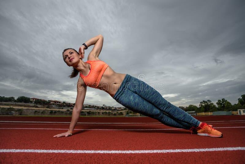 Sportliches Mädchen, das Vasisthasana beim Üben von Yoga tut lizenzfreie stockbilder
