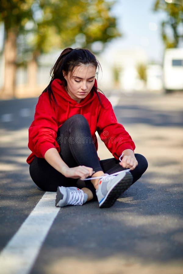 Sportliches Mädchen sitzt aus den Grund an einem sonnigen Herbsttag stockfoto