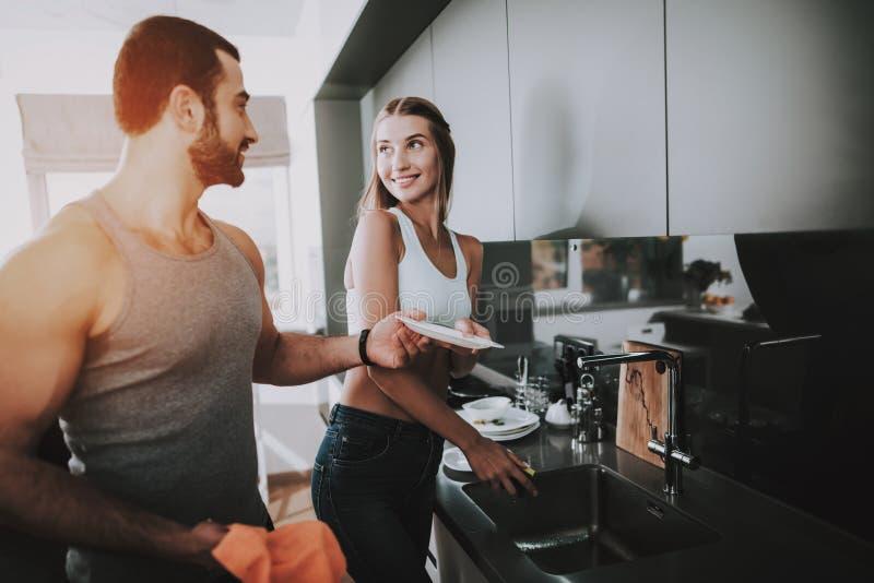 Sportliches Paar wäscht einen Teller an der Küche stockfoto