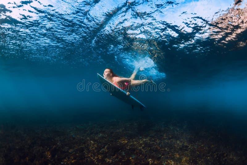 Sportliches Surferfrauentauchen Unterwasser mit darunter Welle stockfotos