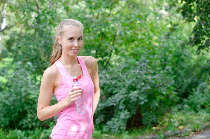 Sportliches Trinkwasser der jungen Frau von der Flasche Handeln den Sport im Freien stockfotos