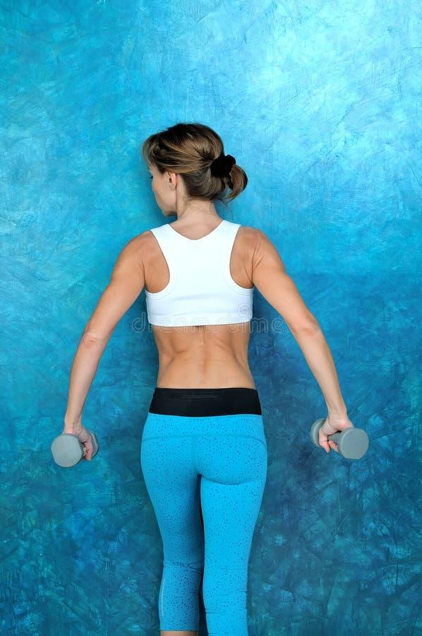 Sportmädchen, das Trainingsübung mit Dummköpfen tut stockfotos