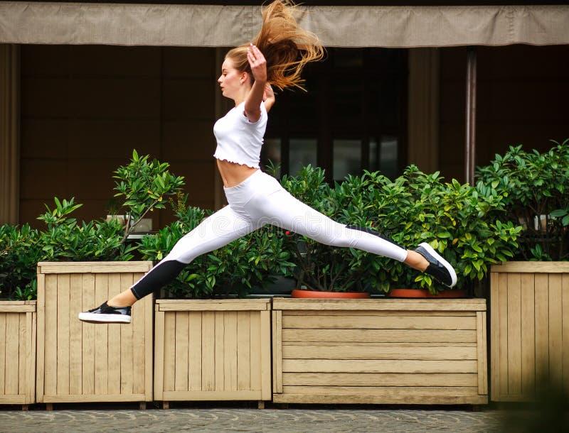 Sportmädchenturner, der im Flug an der Fassade des Straßenhauses springt stockfotografie