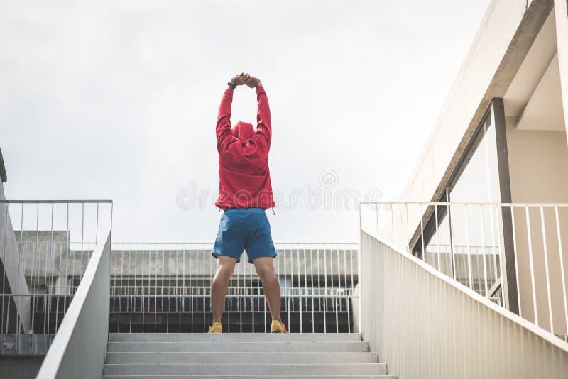 Sportman dans le capot rouge faisant l'exercice près des étapes extérieures photos libres de droits