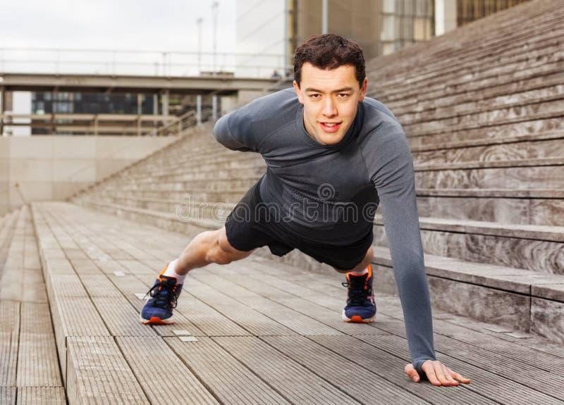 Sportman die opdrukoefeningen op één hand in openlucht doen royalty-vrije stock fotografie