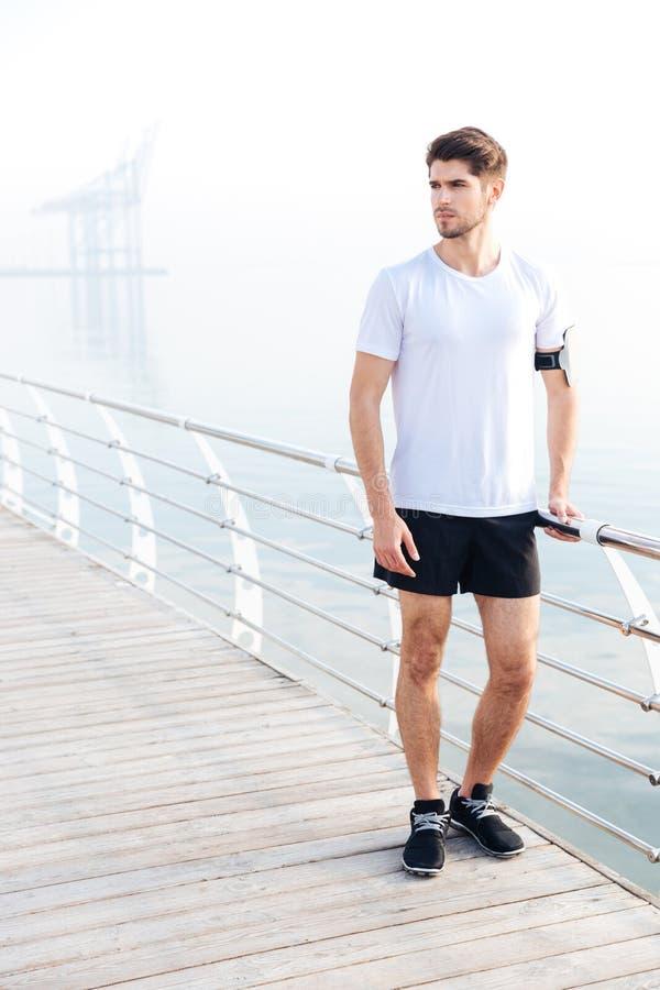 Sportman die zich op pijler dichtbij het overzees bevinden stock fotografie