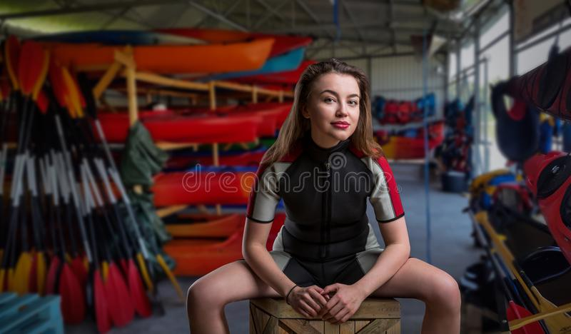 Sportman femenino en el wetsuit, barcos en fondo imágenes de archivo libres de regalías