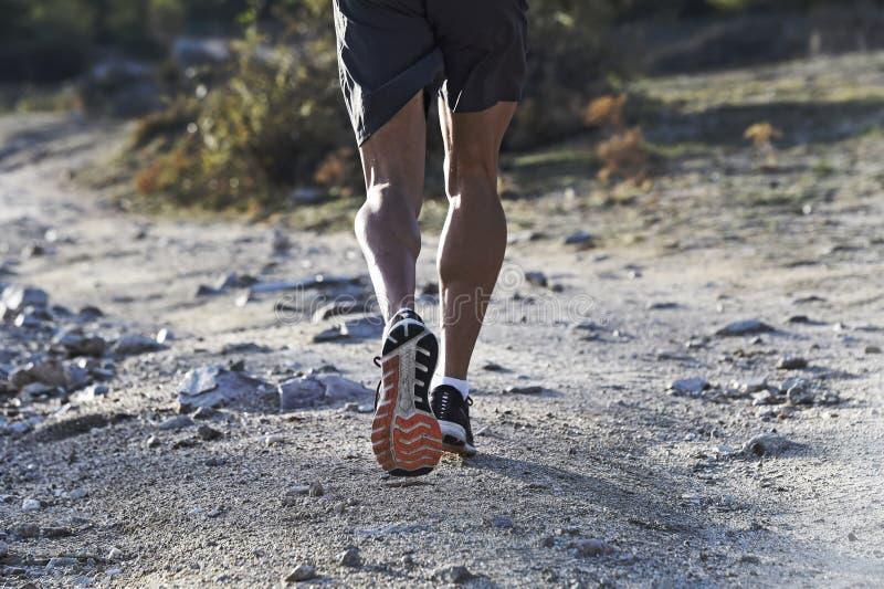 Sportman med rev sönder idrotts- och muskulösa ben som kör av vägen i jogga utbildningsgenomkörare på bygd i höstbakgrund arkivbild