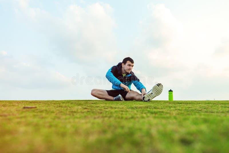 Sportman met een fles van water zitting en het doen van het verwarmen uitrekkende oefening in het park royalty-vrije stock foto