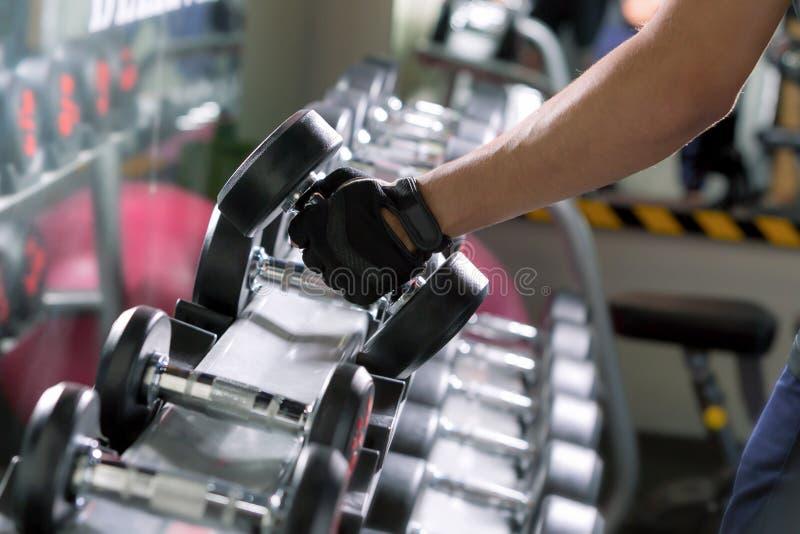 Sportman som gör en-arm hantelrader av metall i modern idrottshall arkivbild