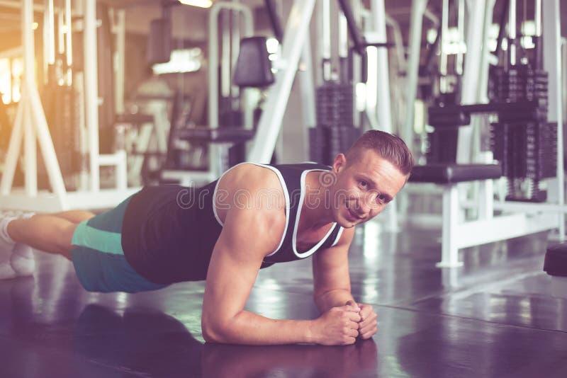 Sportman som gör plankaövningar som utbildar full längd för kärna i idrottshallen, sunt livsstilbegrepp arkivbilder
