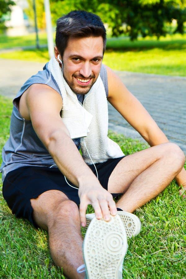 Sportman som sträcker på parkera arkivfoto