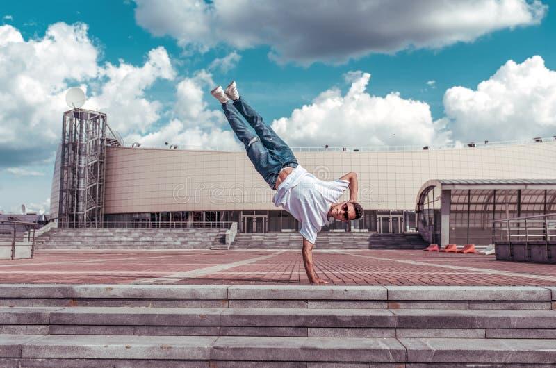 Sportman, staat op één arm, een jonge man een danser, een lagere pauze, dansend in beweging in de zomer in de stad tegen stock fotografie