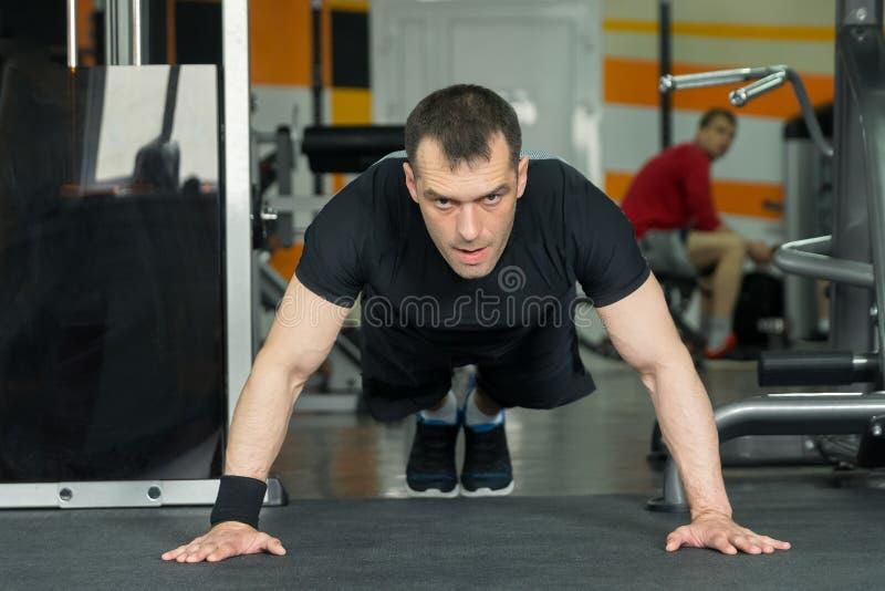 Sportman zwarte borrels dragen en t-shirt die opdrukoefeningen doen royalty-vrije stock foto