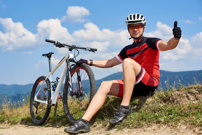 Sportmanfietser in sportkleding en helmzitting dichtbij zijn bergfiets op grasrijke kant van de weg stock afbeelding