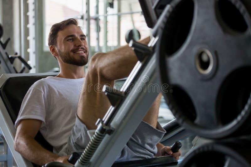 Sportmann, der ?bungen mit Beinpressemaschine in der Eignungsturnhalle tut workout Training lizenzfreie stockfotografie