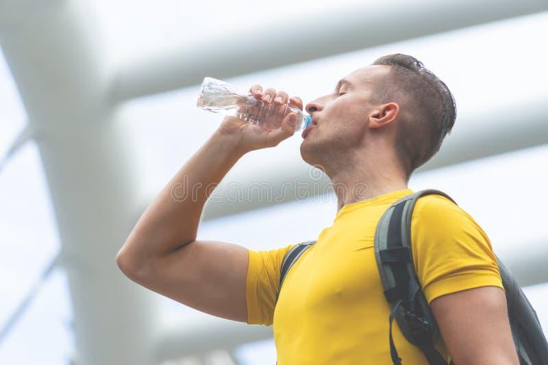 Sportmann im Gelb ist Getränkwasser Stadt in der im Freien lizenzfreie stockfotos