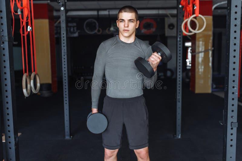Sportmannen lyfter vikter i utbildning i idrottshallen, morgonutbildning royaltyfri fotografi