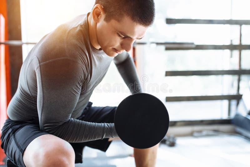 Sportmannen lyfter vikter i utbildning i idrottshallen, morgonutbildning fotografering för bildbyråer