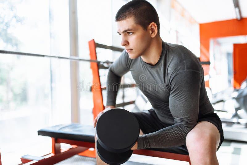 Sportmannen lyfter vikter i utbildning i idrottshallen, morgonutbildning royaltyfri foto