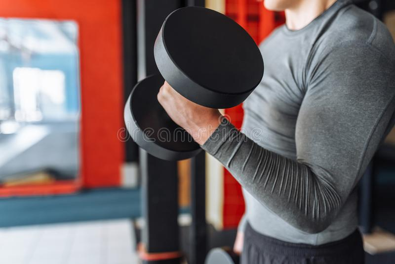 Sportmannen lyfter vikter i utbildning i idrottshallen, räcker närbild arkivfoto
