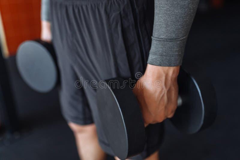 Sportmannen lyfter vikter i utbildning i idrottshallen, räcker närbild arkivbild