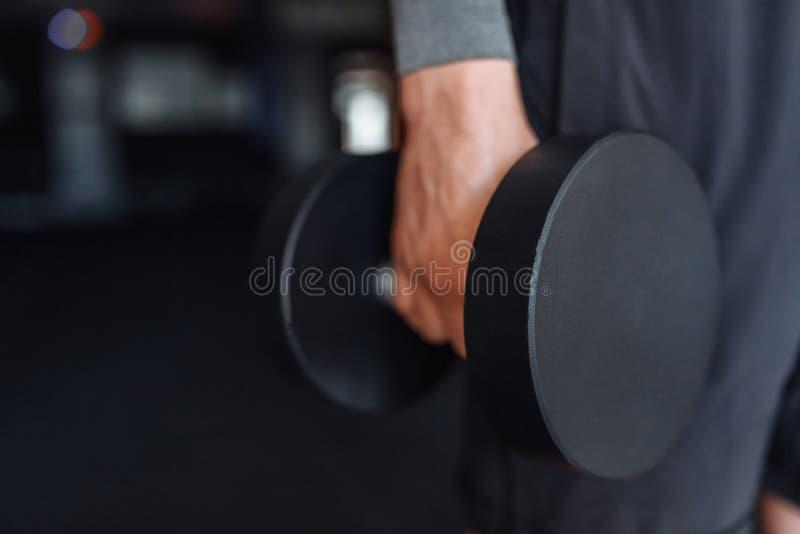 Sportmannen lyfter vikter i utbildning i idrottshallen, räcker närbild arkivbilder
