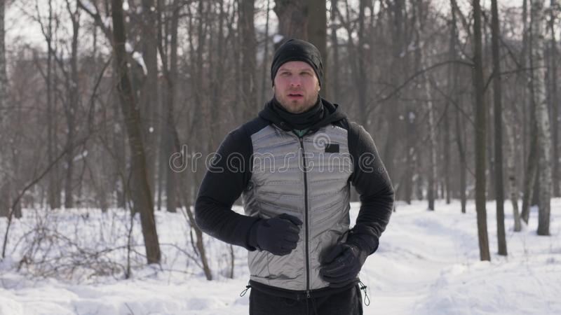 Sportmanspring i vinterstad parkerar under morgon joggar Jogga i vinterskog fotografering för bildbyråer