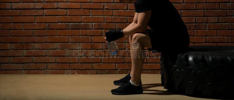 Sportmanzitting met een fles water op een band die na een training op een bakstenen muurachtergrond rusten stock afbeeldingen