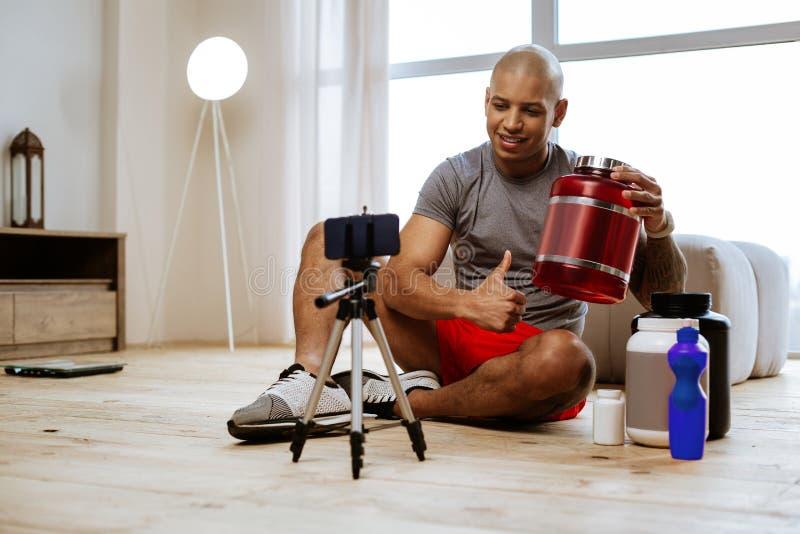 Sportmanzitting op de blog van de vloerfilm over dieetproteïne stock afbeelding