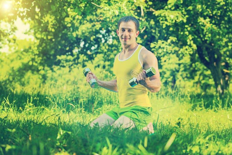 Sportmanzitting op gras en het opheffen gewichten in ins van het parkgebied royalty-vrije stock afbeeldingen