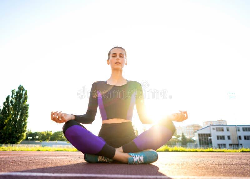 Sportmeisje bezette yoga in een opwarming bij het stadion bij zonsondergang stock afbeeldingen