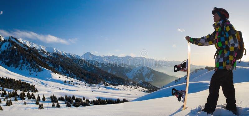 Sportmens in sneeuwbergen bij zonsondergang stock afbeelding