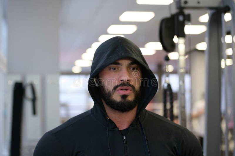 Sportmotivierungskonzept eines jungen bärtigen, kaukasischen starken Mannes im Fitnessraum mit geistiger Konzentration lizenzfreies stockbild